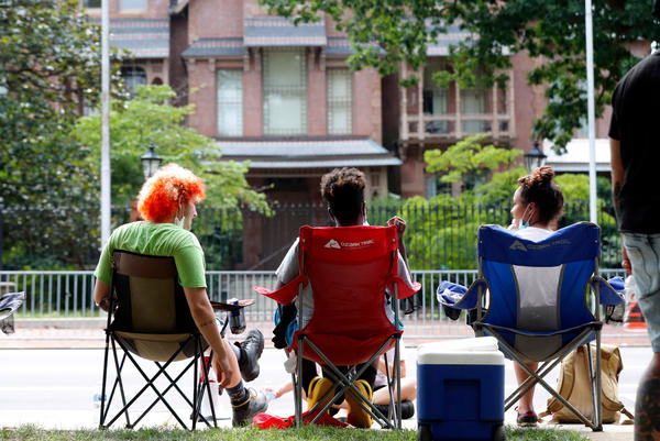 Protesters sit outside the N.C. Executive Mansion in Raleigh, N.C., Tuesday morning, June 30, 2020. They camped out overnight Monday to protest a new bill that further limits public access to death investigation records.