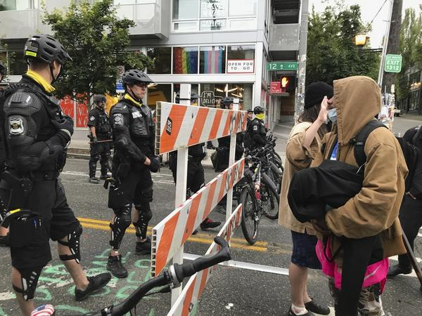 Protesters stand across from Seattle officers early Wednesday in a road in the Capitol Hill Organized Protest zone. Police started taking down demonstrators' tents in the protest zone after Seattle's mayor ordered it to be cleared.