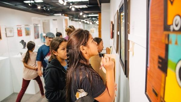 Students examine artworks on display at the Heritage Center at Red Cloud.