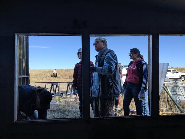Archaeologist Bob Brunswig, center, inspects the outside of a building that used to be the gas station.