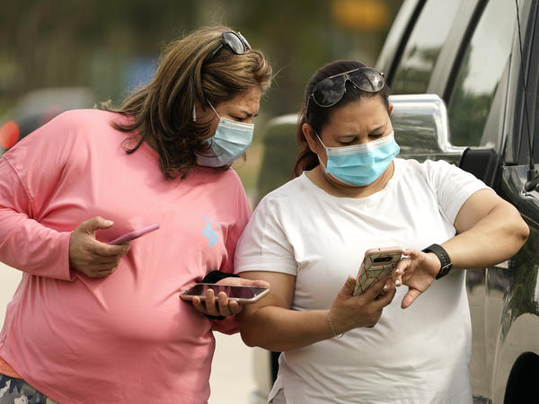 Women wear masks in Houston on Wednesday. Harris County requires any business providing goods or services to require all employees and visitors to wear face coverings in areas of close proximity to co-workers or the public, at least through Aug. 26.