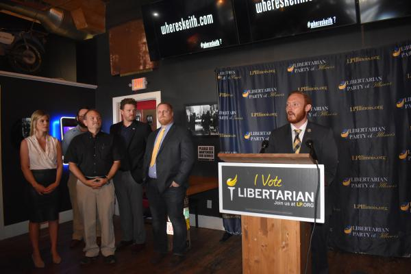Donny Henry, chairman of the Libertarian Party of Greater Peoria, stands at the podium to introduce the party's candidates for area races at a press event at Mack's on Thursday, July 2, 2020.