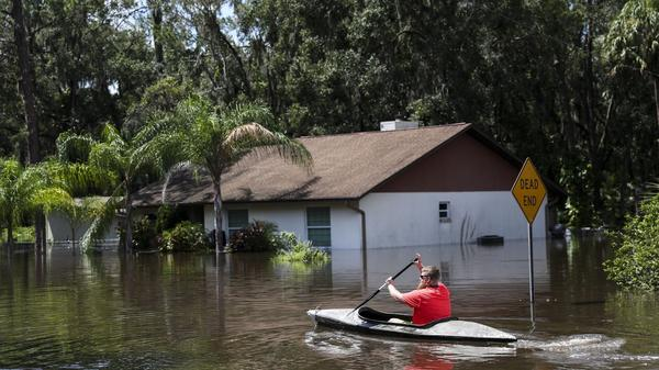 Justin Lyons, 29, kayaks back to his Valrico home for more belongings, in flood waters from the Alafia River, after Hurricane Irma in September 2017.