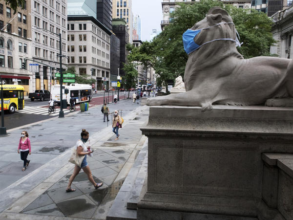 A face mask covers the mouth and nose of one of the iconic lion statues in front of the New York Public Library Main Branch on Wednesday, July 1, 2020, in New York, amid the coronavirus pandemic.