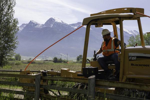 A Blackfoot Communications employee installs conduit for fiber optic cable near St. Ignatius, Montana, June 2020.