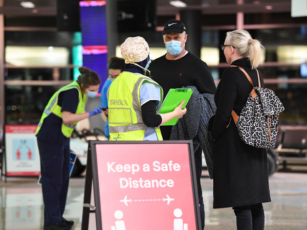 New South Wales health officials interview passengers as they arrive from a Qantas flight that flew from Melbourne at Sydney Airport in July.