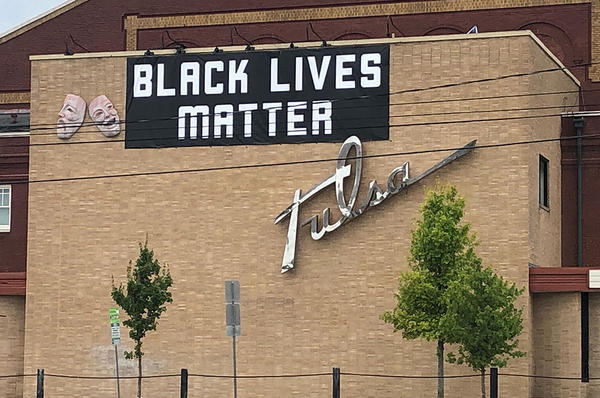 A Black Lives Matter banner hangs on Tulsa Theater in Tulsa, Okla. The venue was formerly named Brady Theater after Tate Brady, a member of the Ku Klux Klan.