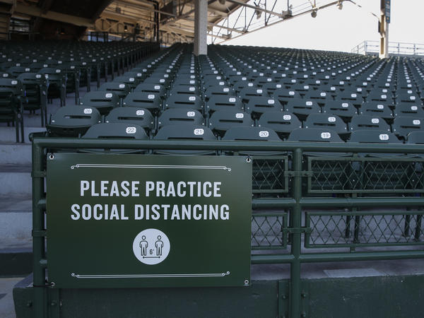 A sign inside Wrigley Field requires guest to practice social distancing amid the coronavirus pandemic during Chicago Cubs baseball training camp on July 5  in Chicago.