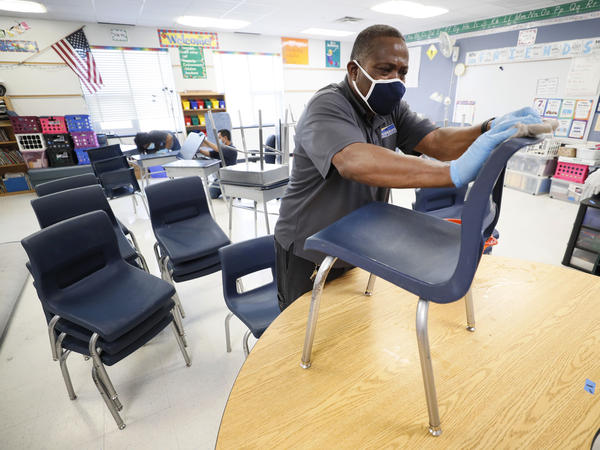 Tracy Harris, a Des Moines Public Schools custodian, cleans chairs at a local elementary school in early July.