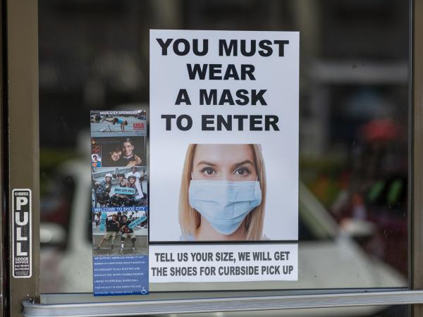 Masks are required for entry to a shoe store in Glendale, Calif. Most people follow guidelines to wear masks when they enter retail stores and restaurants, but some customers don't comply.