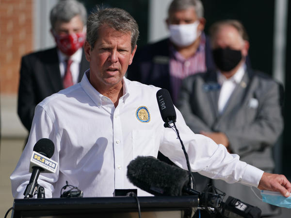 Georgia Gov. Brian Kemp holds a protective mask while speaking during a 'Wear A Mask' tour stop in Dalton, Georgia, earlier this month.