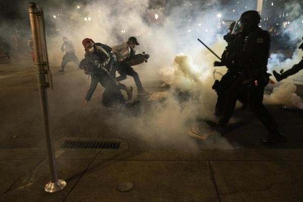 <p>Protesters scramble to get away from approaching police firing tear gas and impact munitions in downtown Portland, Ore., July 4, 2020, during demonstrations against systemic racism and police violence.</p>