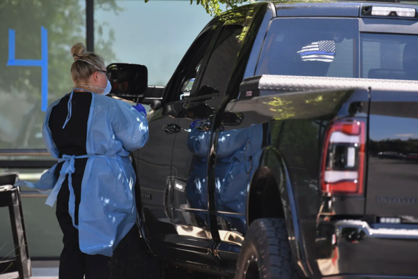 A health care worker talks to a potential COVID-19 patient at a drive-through testing site at an Austin Emergency Center on Wednesday.