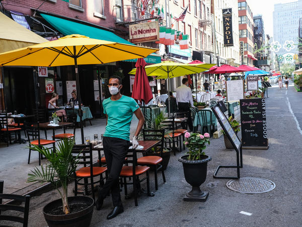 People dine outdoors on July Fourth in Manhattan's Little Italy.