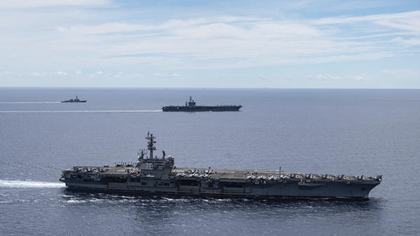 The USS Ronald Reagan (foreground) and the USS Nimitz Carrier Strike Groups sail together in formation in the South China Sea on July 6. China has accused the U.S. of flexing its military muscles by conducting joint exercises with two U.S. aircraft carrier groups in the strategic waterway.