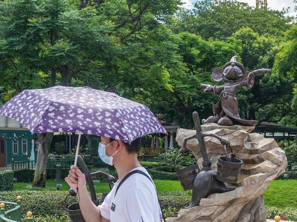 A visitor wearing a protective mask walks past a statue of Mickey Mouse at the Hong Kong Disneyland Resort on June 18, the day it initially reopened. The amusement park will close again on Wednesday.