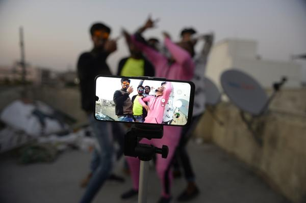 Youths perform in front of a cellphone camera while making a TikTok video on the roof of their residence in Hyderabad, India, in February. India's government has banned 59 Chinese-owned apps including TikTok.