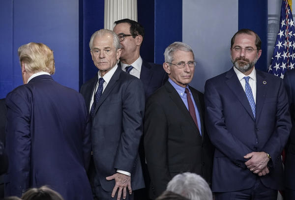White House economic adviser Peter Navarro (center, left) and Dr. Anthony Fauci, director of the National Institute of Allergy and Infectious Diseases, stand back to back after a White House Coronavirus Task Force briefing on March 9. Navarro wrote an opinion article this week criticizing Fauci.