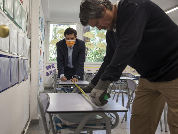 Gonzalo Inclán and Enfrén Carreño of the Liceo Europeo school just outside of Madrid, Spain measure the space between desks in May.