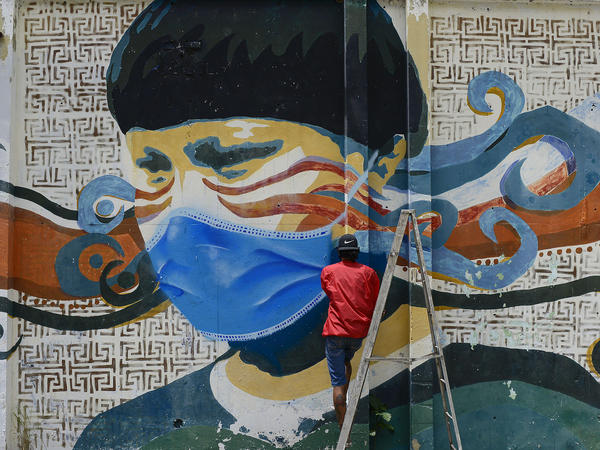 A street artist spray-paints a protective face mask over an old mural featuring a Venezuelan Indigenous man in Caracas, Venezuela, on Saturday. Globally, new daily cases hit an all-time high on Saturday, the World Health Organization reports.