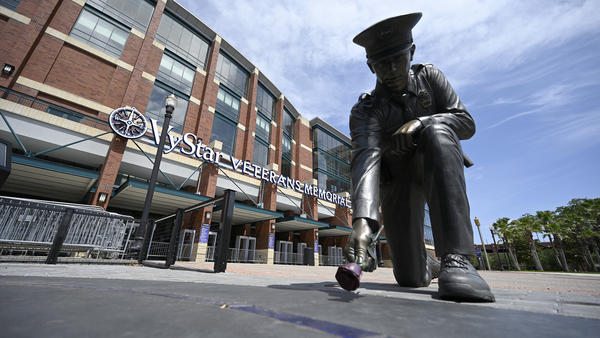 A statue of a police officer placing a rose on the ground seen outside of VyStar Veterans Memorial Arena, one Jacksonville, Fla., venue for the August Republican National Convention.