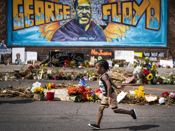 The Minnesota Legislature has approved a bill to revise rules on police use of force in response to the killing of George Floyd. Here, a boy runs past a mural at a memorial to Floyd outside Cup Foods.