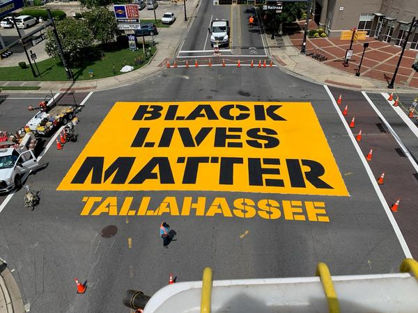 A large, black and yellow sign on the street reads Black Lives Matter