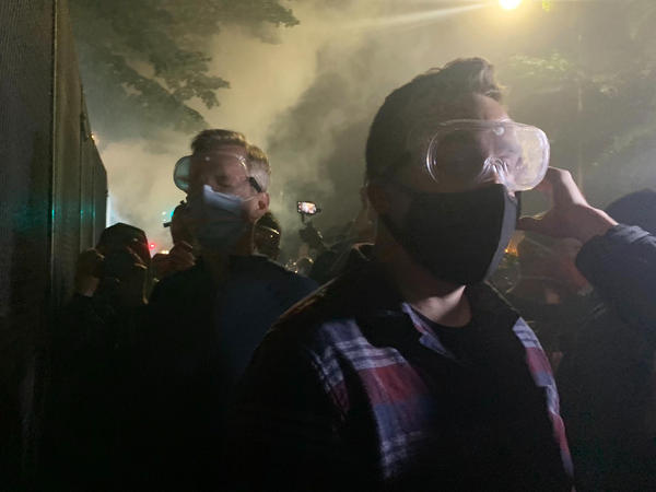 Mayor Ted Wheeler (in dark shirt at left) stands at a fence outside the Mark O. Hatfield U.S Courthouse in Portland, Ore., as federal officers deploy tear gas Wednesday night. People protesting police violence and systemic racism have faced tear gas, impact munitions and other dispersal tactics by the Portland Police Bureau and federal law enforcement.