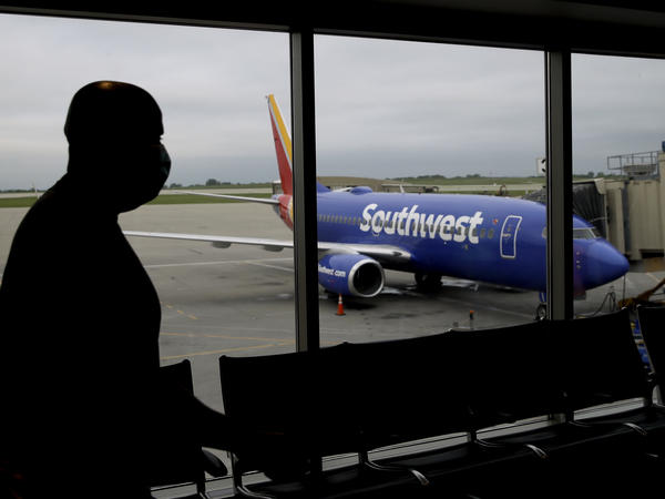 A man wearing a mask prepares to board a Southwest Airlines flight at Kansas City International airport in Kansas City, Mo. Southwest and American Airlines are tightening their mask requirements at the end of July by doing away with exemptions for travelers over the age of 2.