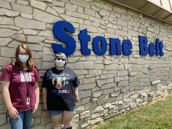Sage Wright, left, and Mikaela Coppedge, right, stand outside Stone Belt, a nonprofit that supports people with intellectual and developmental disabilities. Coppedge lives and Wright works at Blackstone House, one of Stone Belt's  group homes.