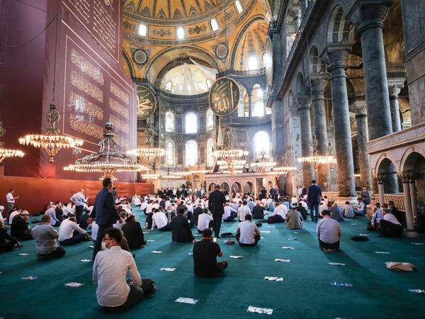People gather to perform Friday prayers at Istanbul's Hagia Sophia for the first time in 86 years.