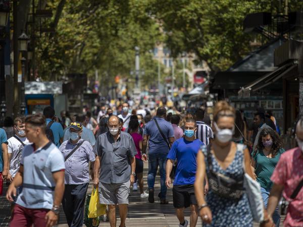 People walk along the Ramblas last week in Barcelona, Spain. The country has seen cases of the coronavirus spike in recent weeks.