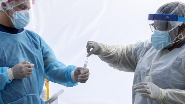 A health worker puts a nasal swab sample into a tube in a tent at a COVID-19 testing site at St. John's Well Child and Family Center in Los Angeles.