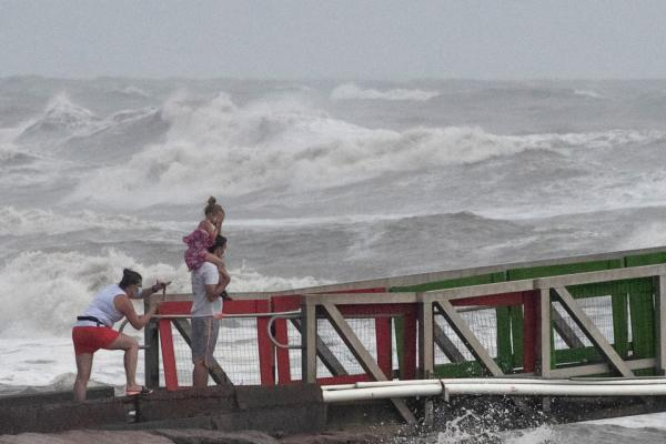 A girl covers her face from strong winds as her family members watch high swells from Hurricane Hanna from a jetty in Galveston, Texas, U.S., July 25, 2020.