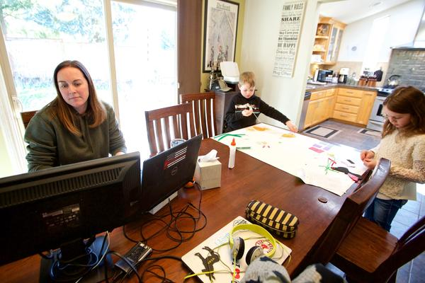 In this Tuesday, March 17, 2020 photo Kim Borton, left, works from home while her children Logan Borton, center, age 6 and Katie Borton, age 7, as they work on an art project in Beaverton, Ore. (Craig Mitchelldyer/AP Photo)