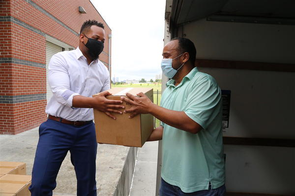 Orleans Parish School Board President Ethan Ashley (left) delivers personal protective equipment to schools on July 24, 2020.