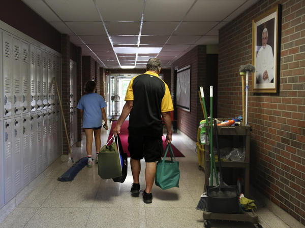 Cesa Pusateri, 12, and her grandfather, Timothy Waxenfelter, principal of Quigley Catholic High School, leave with his collection of speech and debate books after the closure of the school in Baden, Pa., on June 8, 2020. According to the National Catholic Educational Association, at least 100 schools have announced in recent weeks that they won't reopen this fall.