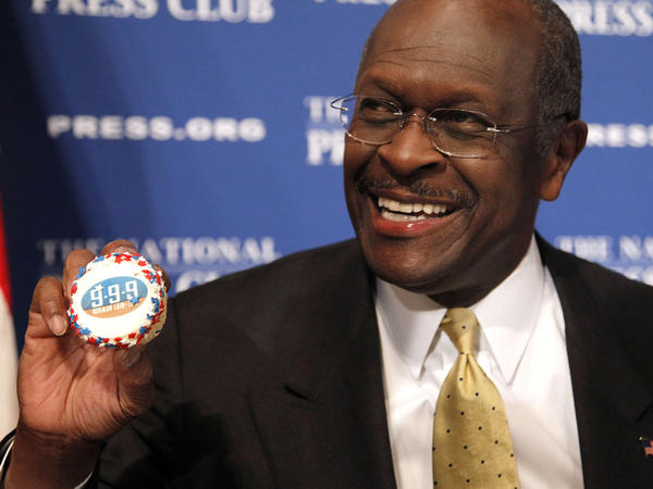 "Herman Cain, then a GOP presidential candidate, holds a muffin bearing his catchphrase ""9-9-9"" tax plan at the National Press Club in Washington in 2011. Cain's death was announced Thursday."