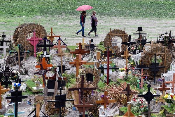 Relatives of those who have died from COVID-19 visit graves in the special area of the Municipal Pantheon of Valle de Chalco, Mexico. The coronavirus has taken a heavy toll on the country, especially its poorest citizens.