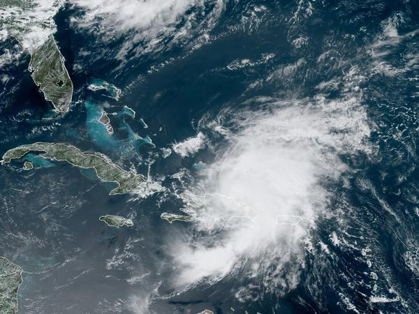 A satellite image from Thursday morning shows Tropical Storm Isaias looming over Puerto Rico and the Dominican Republic. The storm is predicted to drench Florida's east coast over the weekend.