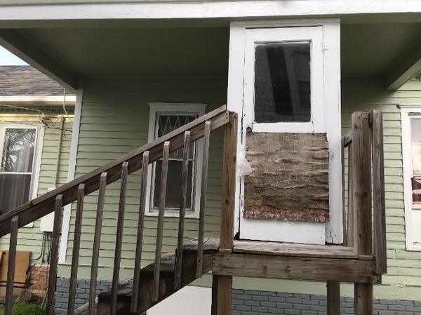 A door with a boarded-up window opens to a platform missing its railing.