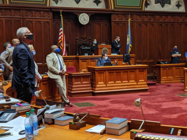Bill author Sen. Gary Winfield (with blue mask) watches the vote in the early hours of Wednesday morning.