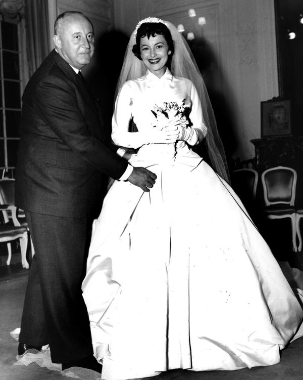 French designer Christian Dior fits de Havilland with a wedding dress for her role in the 1956 film <em>The Ambassador's Daughter</em>.