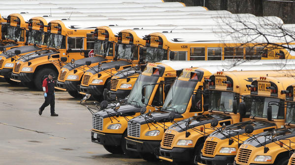 A worker passes public school buses parked at a depot in Manchester, N.H., last month. The state's public school buildings are closed to students through the end of the academic year.