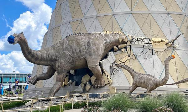 A life-sized dinosaur family wearing masks bursts from the walls of The Children's Museum of Indianapolis, the largest children's museum in the world.
