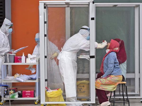 A medical worker collects nasal swab samples this week during a mass test for the coronavirus at North Sumatra University in Medan, Indonesia. The mass test was held after the rector of the university, one of his deputies and a member of the board of trustees tested positive for COVID-19.