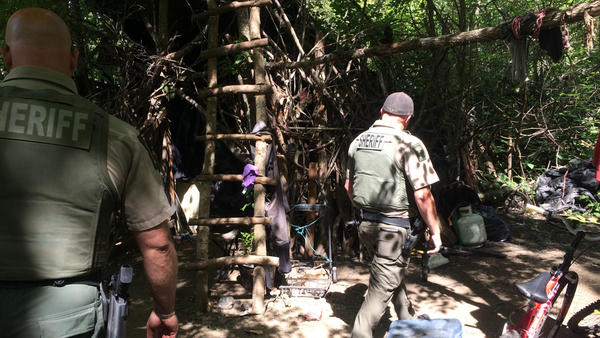 """During their patrol of the Bear Creek Greenway, Jackson County Sheriff's deputies walk through a years-old encampment that deputies call """"the Hobbit House."""""""