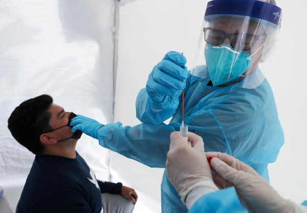 Dr. Glenn Lopez administered a standard test for the coronavirus to Daniel Contreras at a mobile clinic in South Los Angeles last week. Though highly accurate, such tests can take days or more to process.