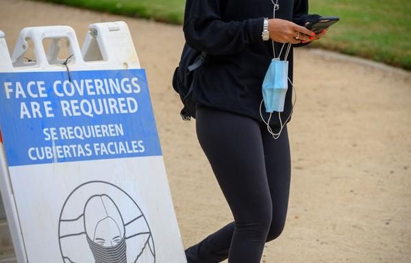 A woman carrying her mask walks past a sign mandating the wearing of face coverings in an effort to control the spread of coronavirus as she walks in Palisades Park in Santa Monica, Calif., on July 25, 2020.