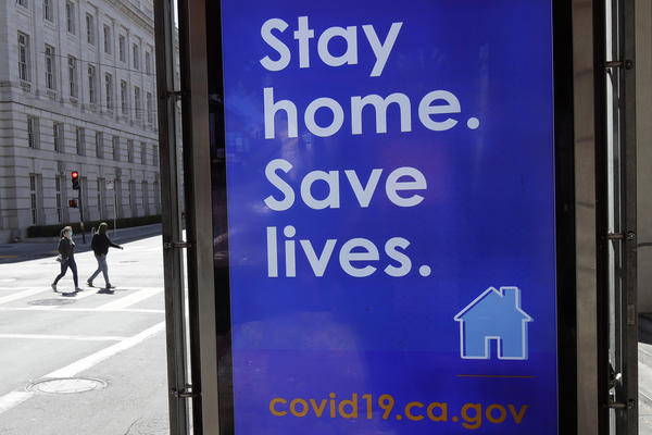 In San Francisco, a poster seen in March urges the public to socially distance in an effort to contain the spread of the coronavirus.